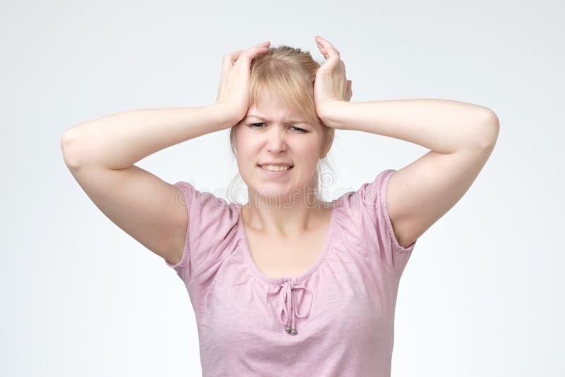 Ung blond tonåring som har allvarlig migrene som lider från förfärlig huvudknip royaltyfri fotografi