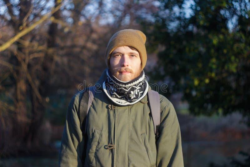 Ung blond vit man med ett skägg som bär en halsduk, en hatt och en ryggsäck royaltyfria foton