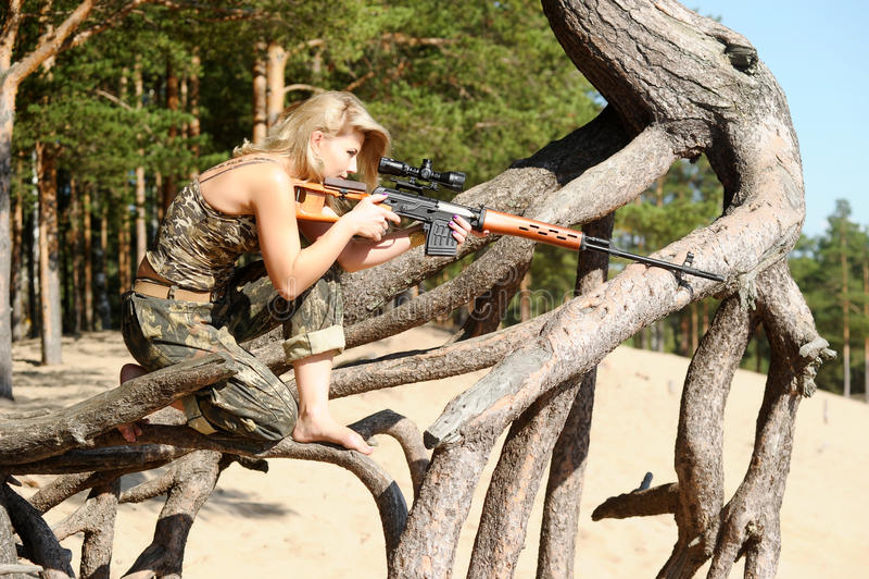 Ung blondin med ett gevär royaltyfri bild