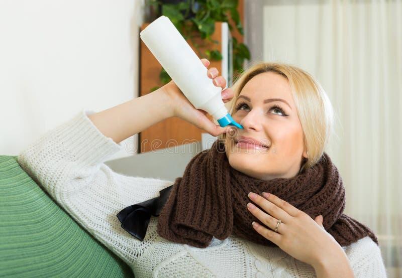 Ung blondin med nasal sprej fotografering för bildbyråer