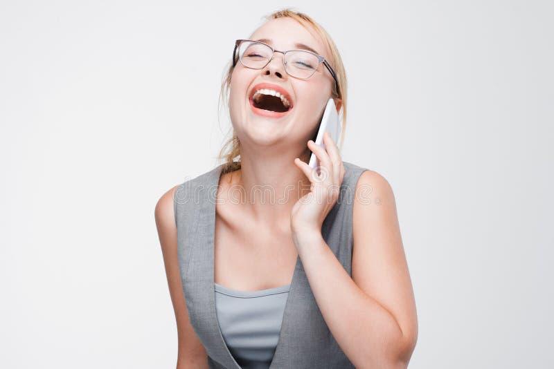 Ung blondin som skrattar ut samtal högt på telefonen fotografering för bildbyråer