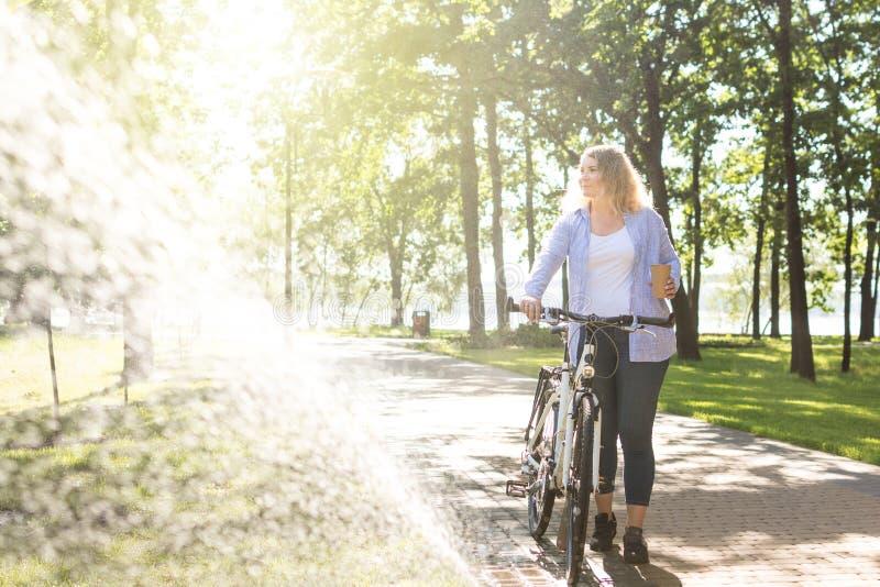 Ung blongekvinna som går hennes cykel i parkera och innehavet per koppen kaffe royaltyfri foto