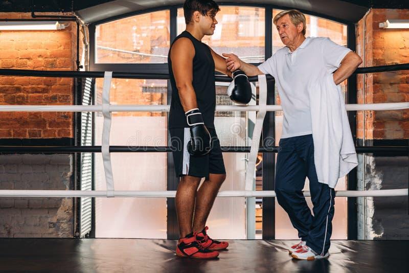 Ung boxare som talar med hans mogna instruktör arkivfoton