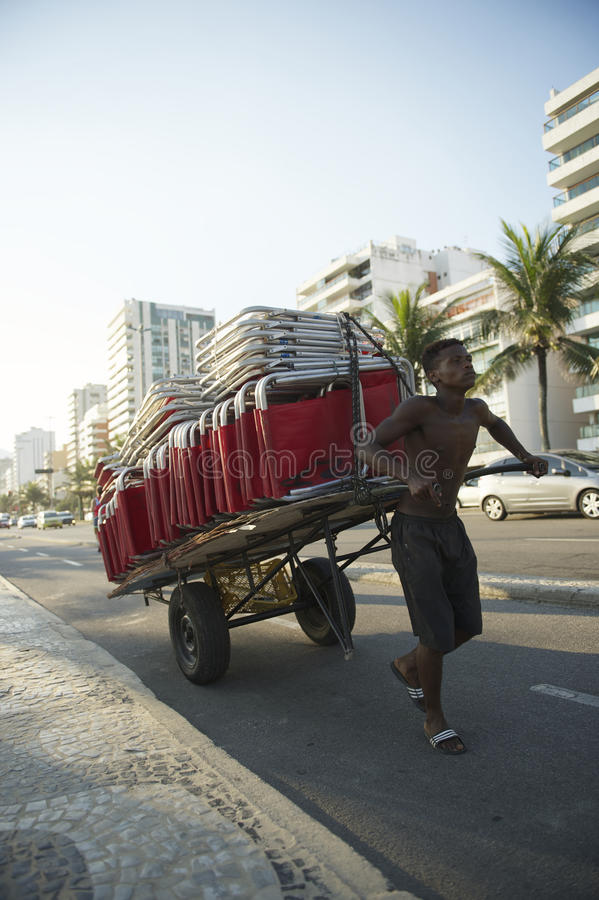 Ung brasiliansk man som drar strandstolar Rio Brazil royaltyfria foton