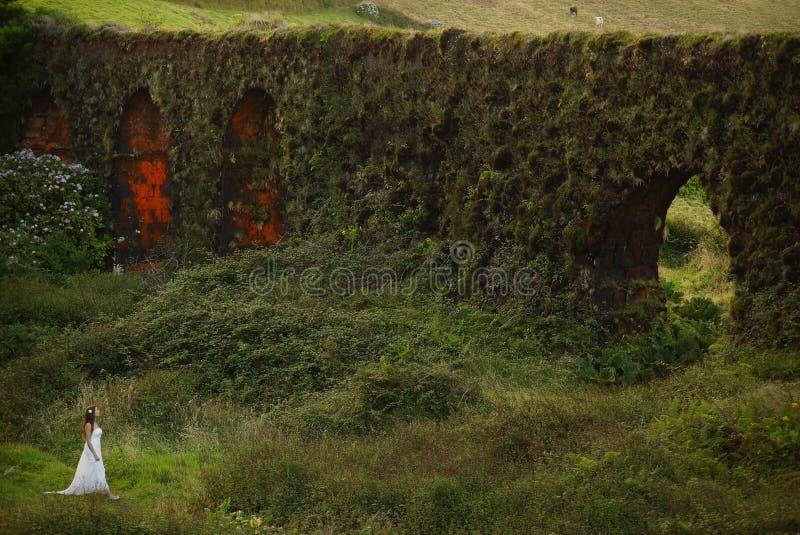 Ung brud nära gräs- brickwall i grönt landskap av Sao Miguel Island arkivfoto