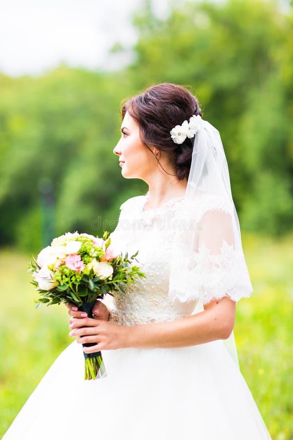 Ung brud som rymmer den stora bröllopbuketten royaltyfria bilder