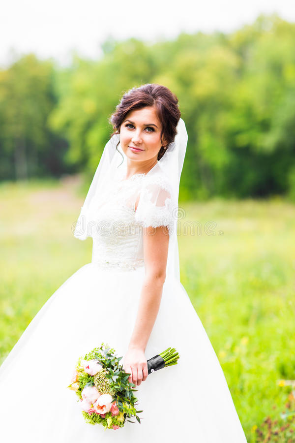 Ung brud som rymmer den stora bröllopbuketten arkivfoton