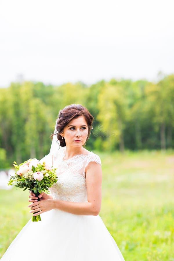 Ung brud som rymmer den stora bröllopbuketten fotografering för bildbyråer