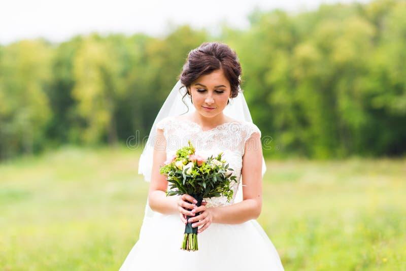 Ung brud som rymmer den stora bröllopbuketten arkivbild