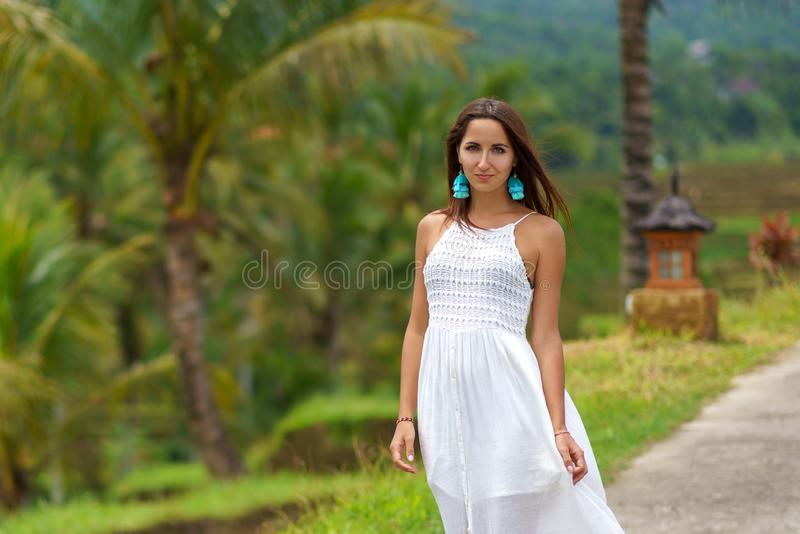 Ung brunbränd kvinna i den vita klänningen som poserar anseende på vägen I bakgrunden ?r palmtr?d och annan tropisk vegetation arkivbilder