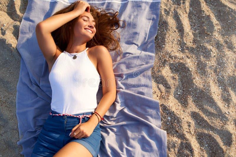 Ung brunbr?nd n?tt kvinna som l?gger i solen p? strandhandduken Kvinnliga l?gner f?r attraktiv stilfull innegrej p? varm sand och arkivfoto