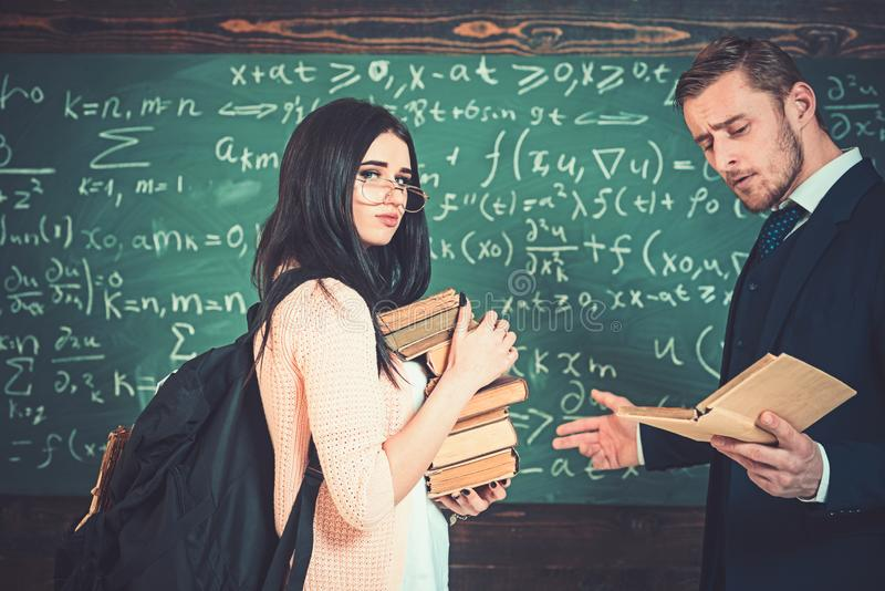 Ung brunett i bärande exponeringsglas för rosa kofta som rymmer högen av böcker, medan professorn läser Lärare och högskola arkivbild