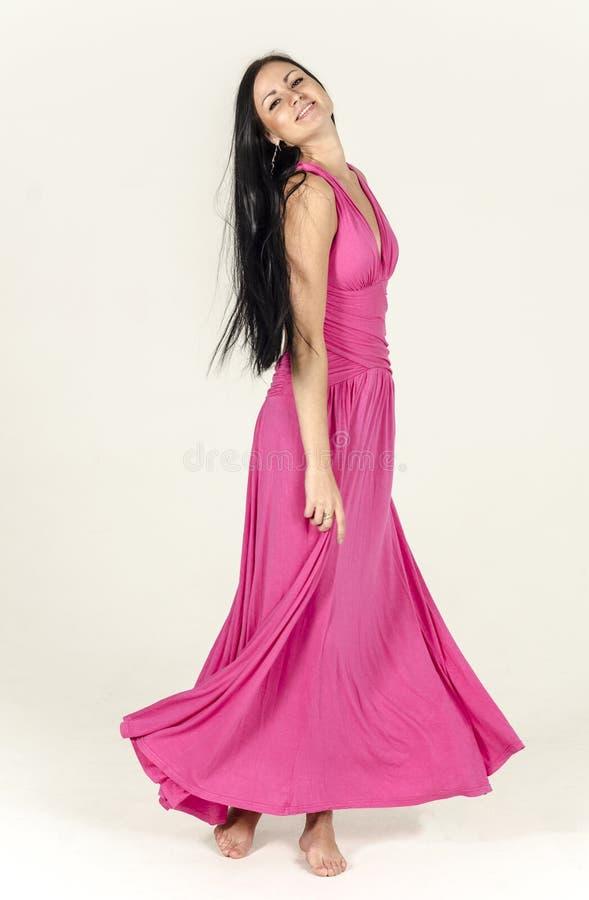 Ung brunett i en lång rosa färgklänning arkivfoton