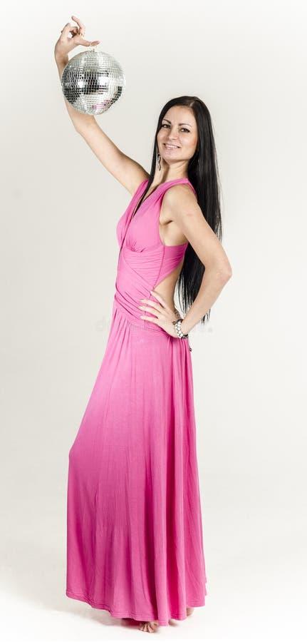 Ung brunett i en lång rosa färgklänning arkivbilder