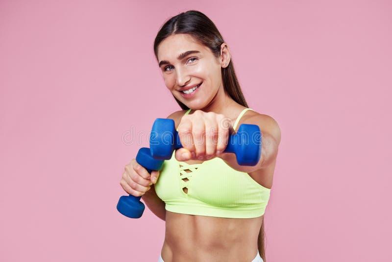 Ung brunett som ler den sportiga kvinnan som poserar eller utbildar med dummklockan i händer, sportdräkt på rosa bakgrund royaltyfri fotografi