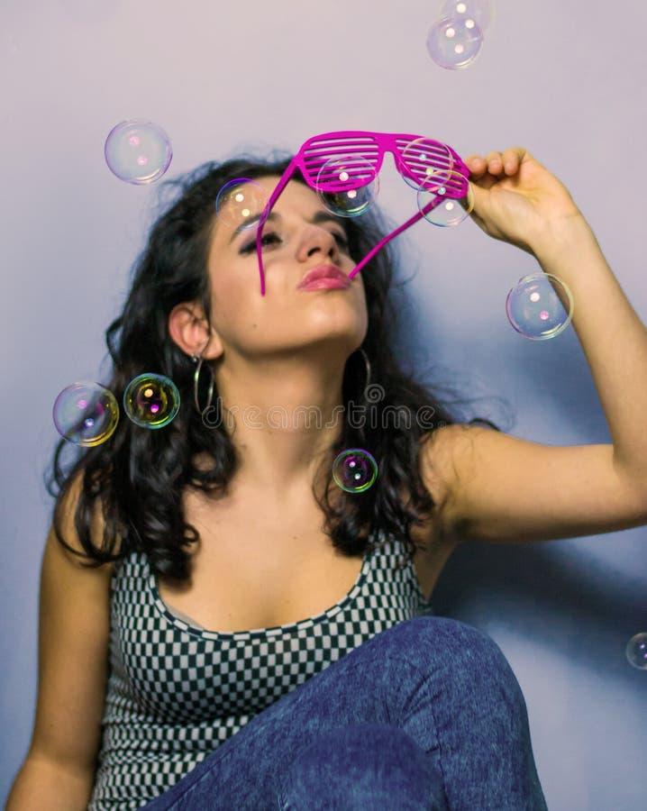 Ung brunett som ser hennes solglasögon fotografering för bildbyråer
