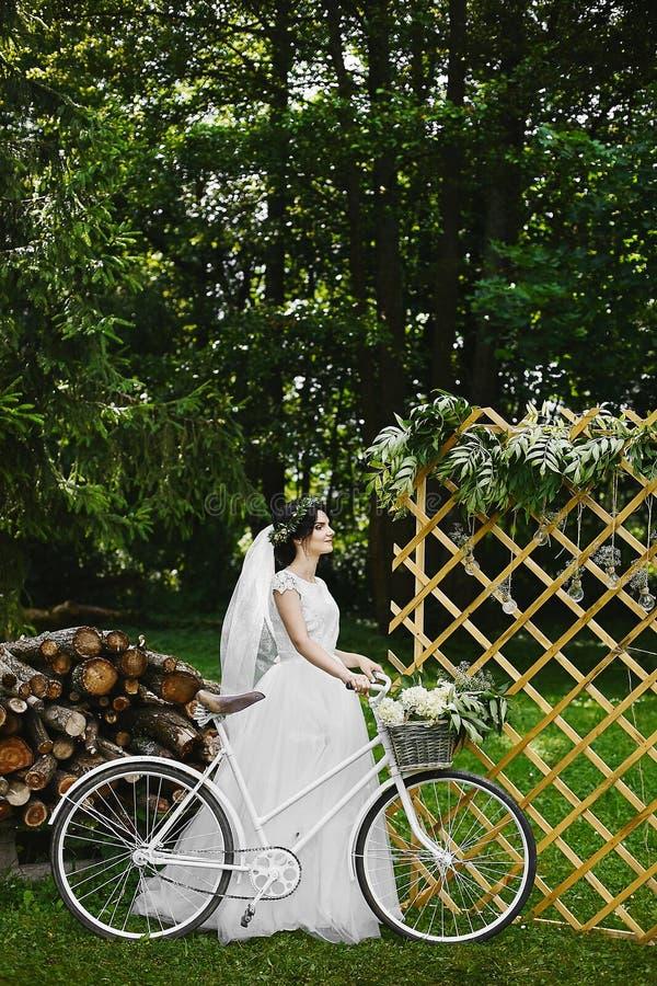 Ung brunettbrud i den vita trendiga klänningen med cykeln och med en bukett av blommor i sommarträdgården royaltyfria foton