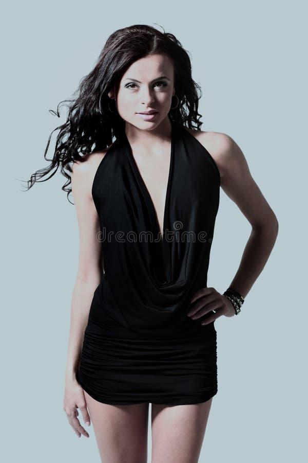 Ung brunettdam i den svarta klänningen som poserar på grå bakgrund royaltyfri fotografi