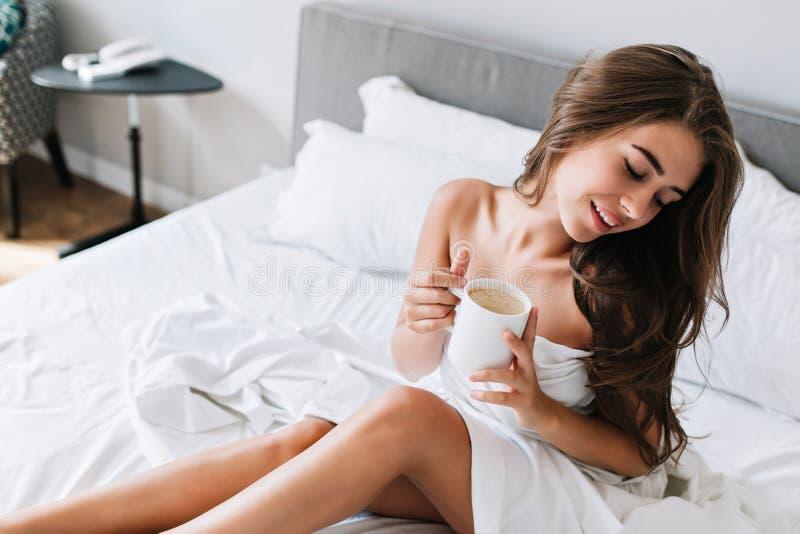 Ung brunettflicka för stående med stygga ben och skuldror på vit säng Hon rymmer koppen, håller ögon stängda, ser royaltyfri foto