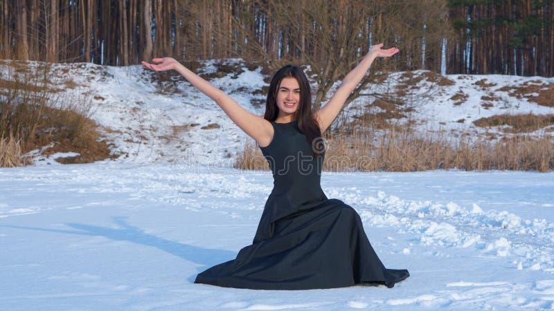 Ung brunettflicka i en lycklig svart klänning le henne händer upp på snöbakgrunden royaltyfria foton