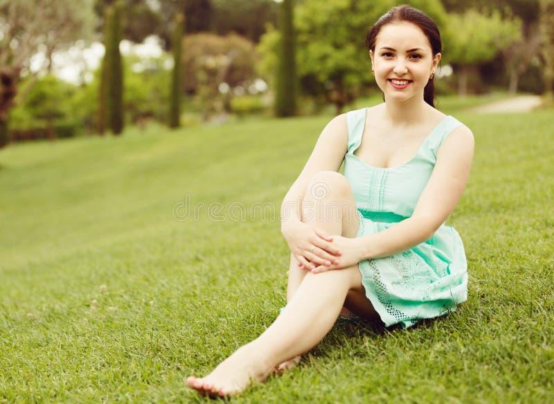 Ung brunettflicka i klänningsammanträde på gräs på trädgården royaltyfri foto