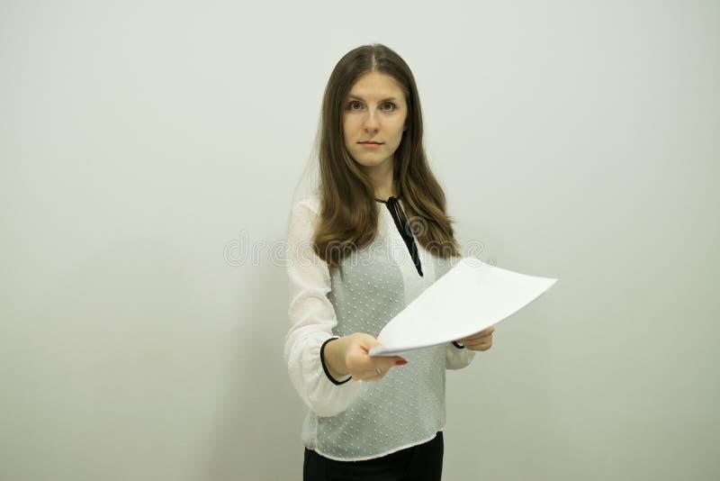 Ung brunettflicka med flödande hårställningar mot en vit vägg som rymmer ark i en hand royaltyfri fotografi