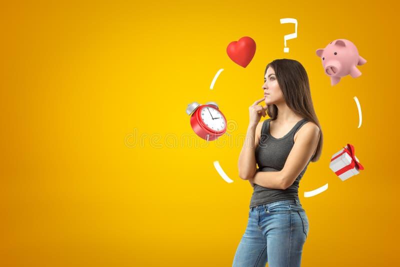 Ung brunettflicka som bär tillfälliga jeans och t-skjorta thinkings med ringklockan, röd hjärta, frågefläck, spargris fotografering för bildbyråer