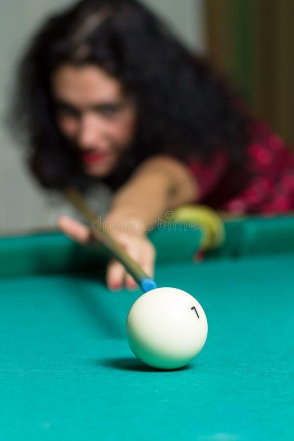 Ung brunettflicka som siktar att klumpa ihop sig spela billiardleken arkivfoto