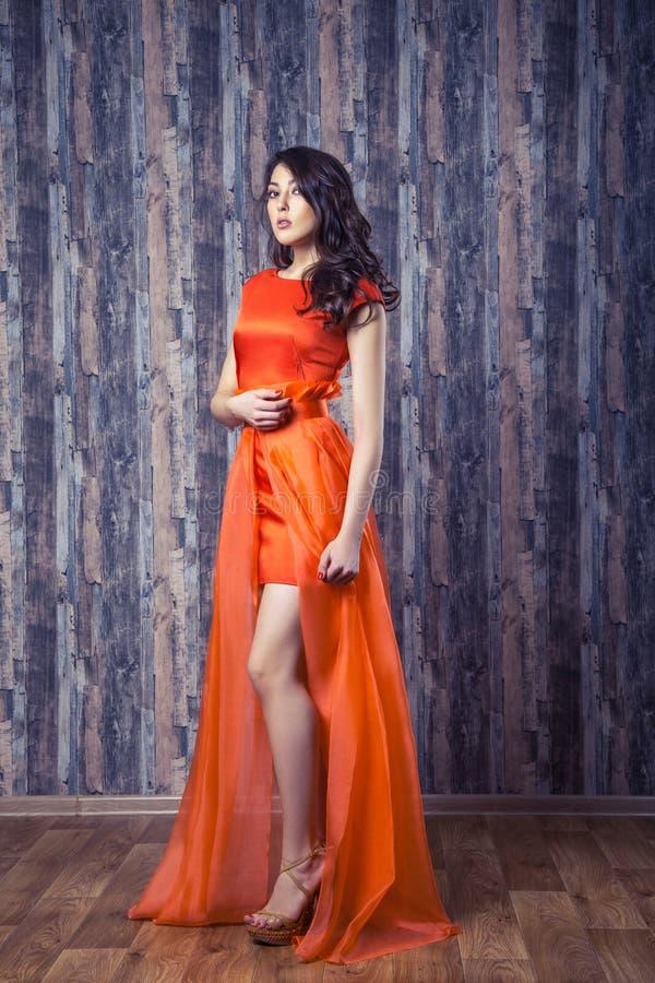 Ung brunettkvinna i den stilfulla orange siden- klänningen som poserar på trä arkivbilder