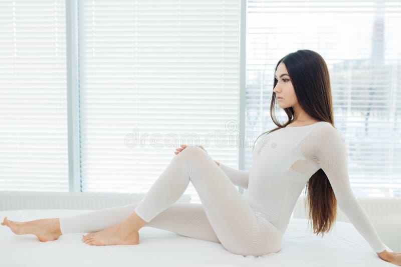 Ung brunettkvinna i den vita banta bodysuiten som väntar på LPG-massageperiod arkivfoton