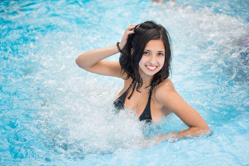 Ung brunettkvinna i en svart baddräkt med ett snövitt leende som kopplar av i en bubbelpool arkivbild