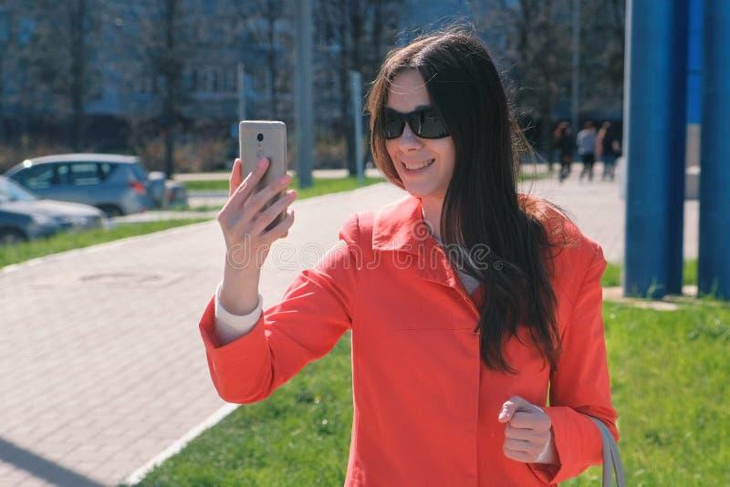 Ung brunettkvinna i solglasögon som talar på videoen som kallar på telefonen bredvid blå byggnad på gatan royaltyfri foto