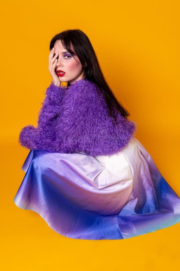 Ung brunettkvinna med färgrik makeup i purpurfärgad tröja arkivfoto