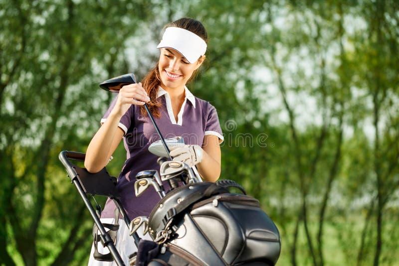 Ung brunettkvinna med golfutrustning royaltyfri foto