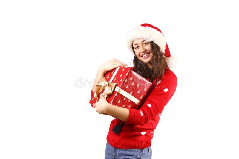 Ung brunettkvinna med långt lockigt hår som bär Santa Claus hattandd som rymmer gåvor fotografering för bildbyråer
