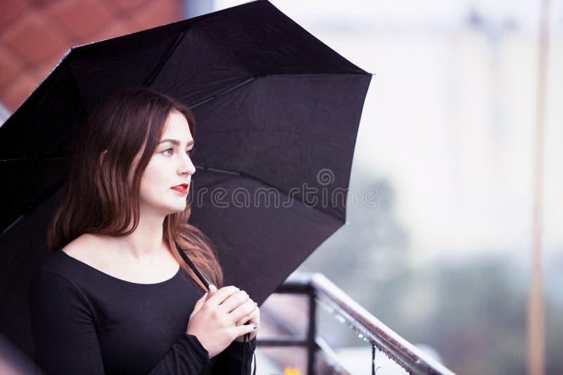 Ung brunettkvinna med paraplyet i regnet arkivbild