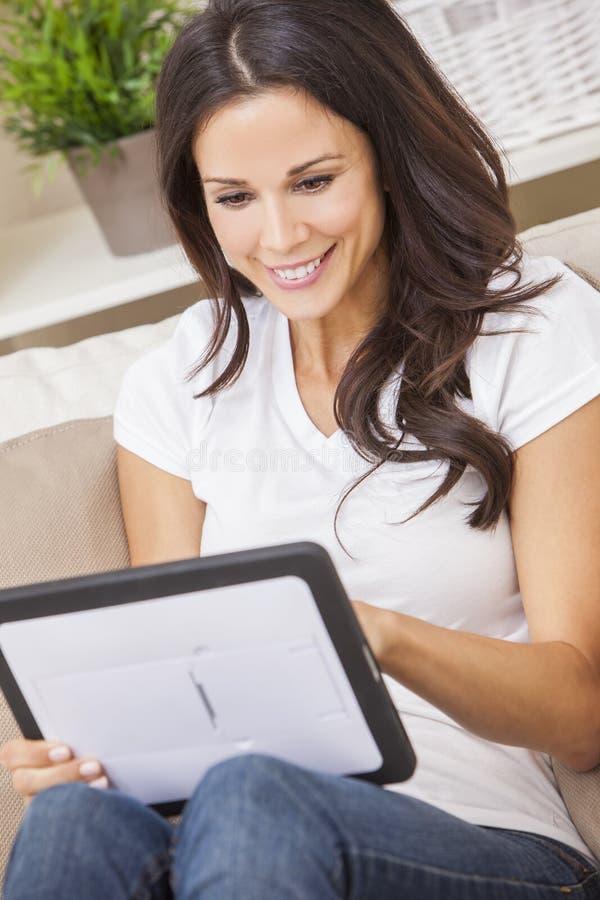 Ung brunettkvinna som hemma använder minnestavladatoren på soffan royaltyfri bild