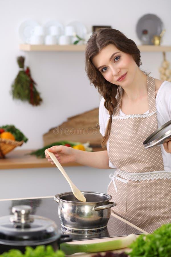 Ung brunettkvinna som lagar mat soppa i kök Hemmafru som rymmer träskeden i hennes hand Mat och hälsobegrepp royaltyfri fotografi