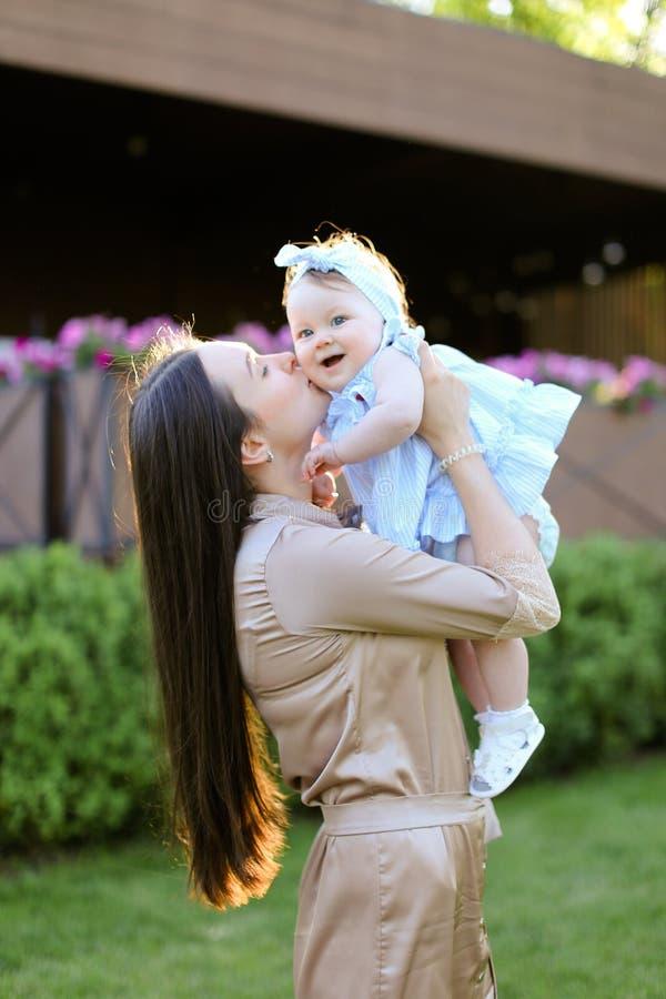Ung brunettkvinna som rymmer och kysser den lilla dottern arkivbild
