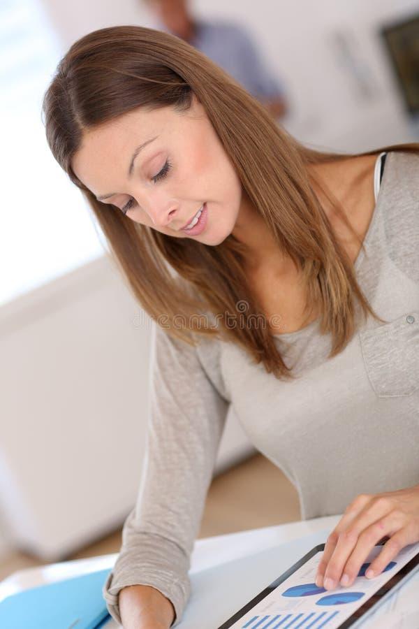 Ung brunettkvinna som ser grafer i ett kontor royaltyfria bilder