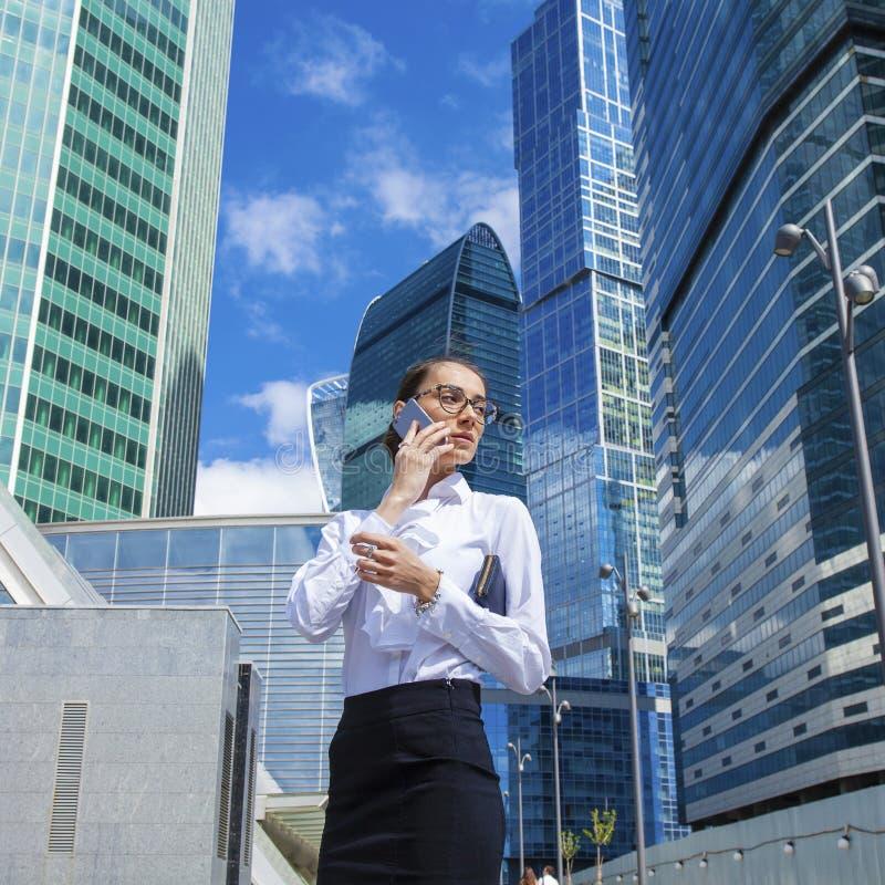 Ung brunettkvinna som stannar till telefonen royaltyfri foto