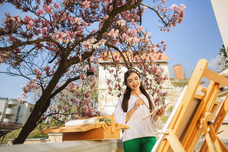 Ung brunettkvinnakonstn?r som rymmer i h?nder en borste och en palett N?ra henne magnoliatr?det och den olika konstutrustningen arkivfoton