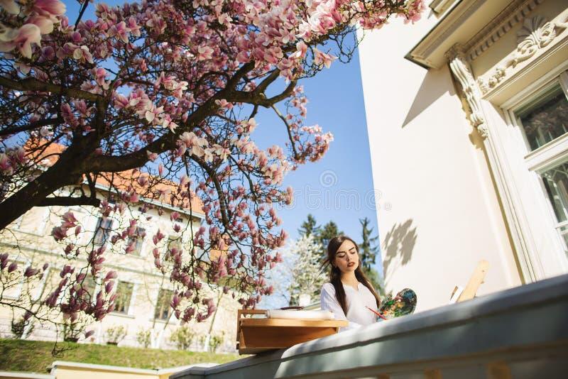 Ung brunettkvinnakonstn?r som rymmer i h?nder en borste och en palett N?ra henne magnoliatr?det och den olika konstutrustningen arkivbilder