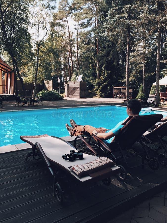 Ung brunettman som lägger på sunbed nära simbassäng med dslrkameran och den elektroniska stabilisatorn royaltyfri bild