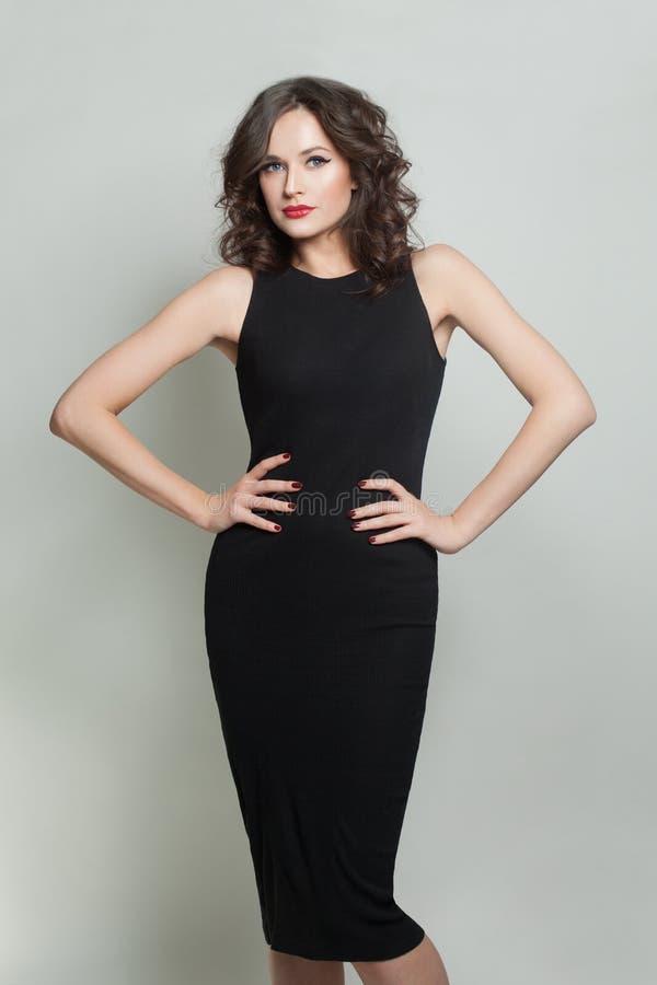 Ung brunettmodellkvinna som bär svart klänninganseende på vit bakgrund arkivbild