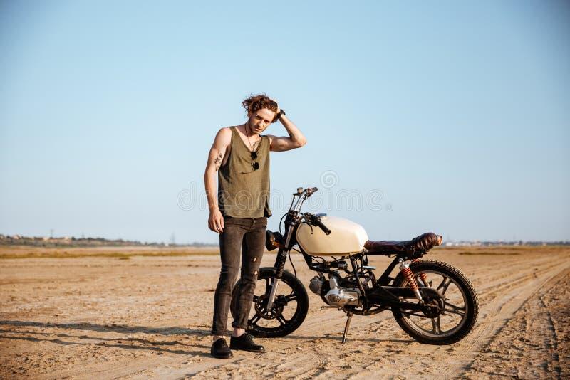 Ung brutal man i svart anseende nära en motorcykel arkivbilder