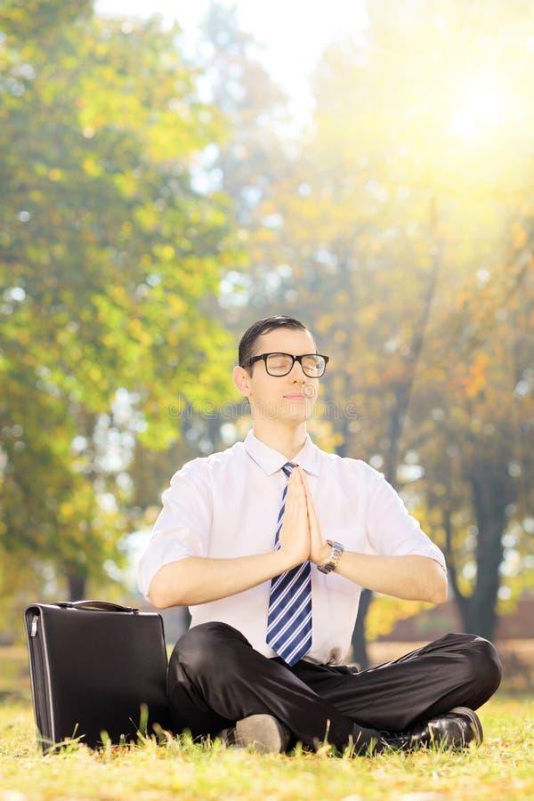 Ung businessperson som gör yoga som placeras på ett gräs i en parkera arkivfoto