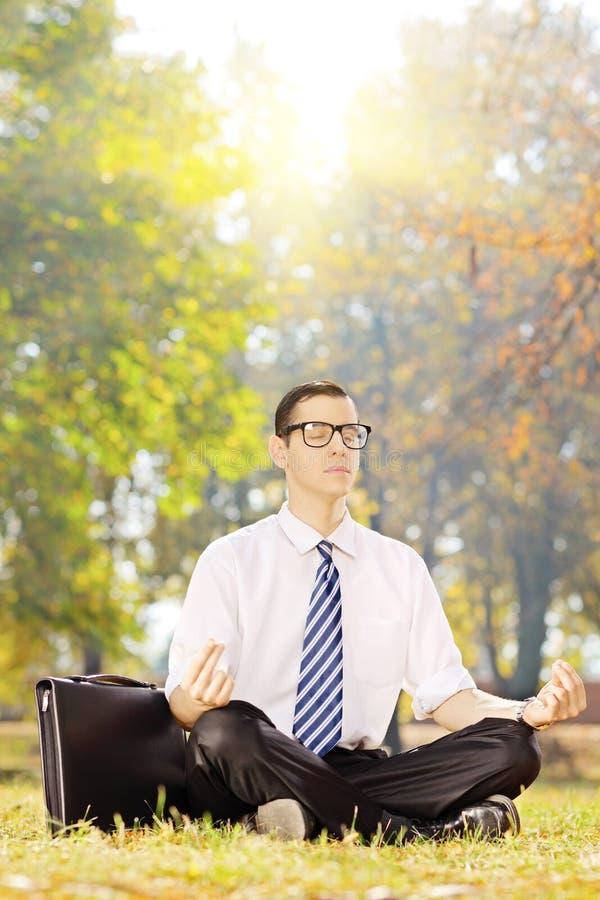 Ung businessperson som placeras på gräs som mediterar på en solig dag arkivfoto