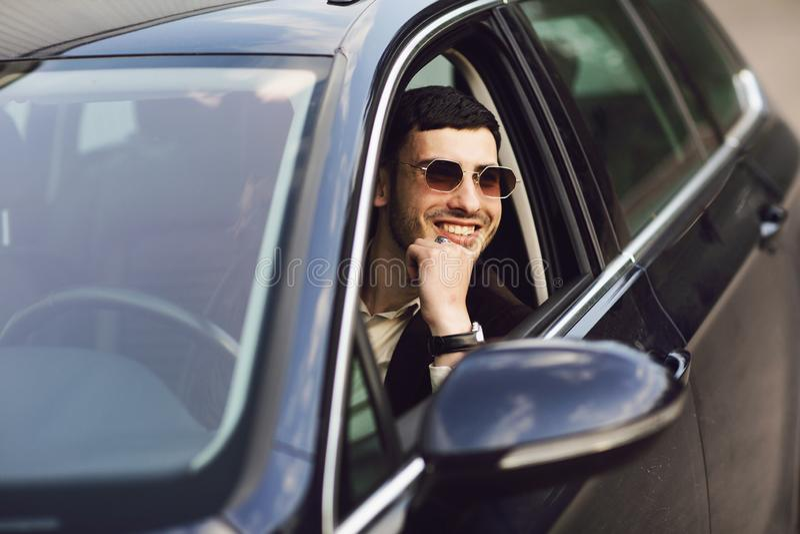 Ung bussinesman i dräkten och svarta exponeringsglas som kör hans bil r r arkivbild