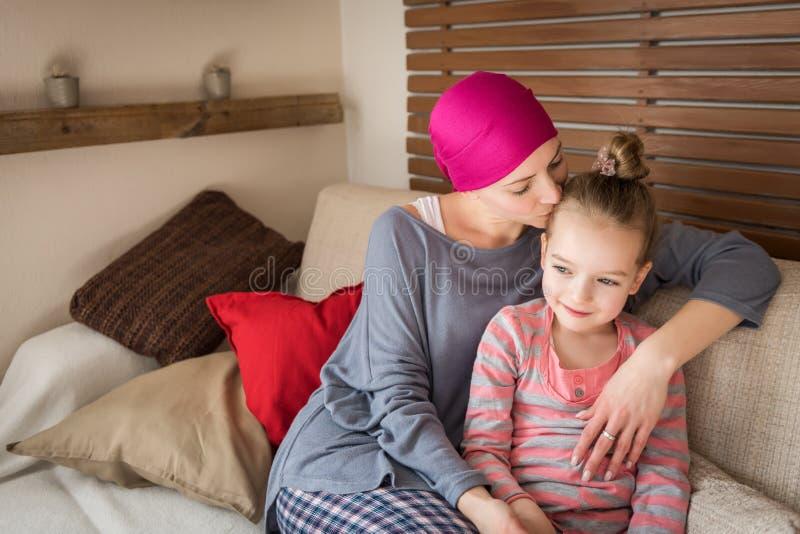Ung cancerpatient för vuxen kvinnlig som spenderar tid med hennes hemmastadda dotter och att koppla av på soffan Cancer- och fami arkivbilder